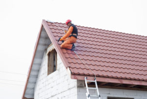 a homeowner at his roof putting some roof repair tips into practice